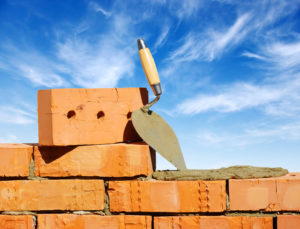 brick wall partially built with tool against blue sky
