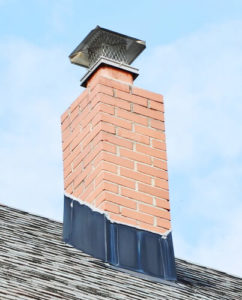 chimney with black flashing and cap against blue sky